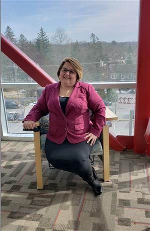 Gina Ross, Director of Student Services - Elementary sitting in a chair in front of window